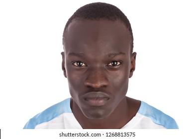 Young handsome Sudanese man close up bland expression piercing eye contact face to camera in white tshirt in landscape format with copy space isolated on white background metaphor for help me
