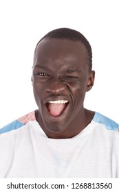 Young handsome Sudanese man face to camera in white tshirt winking, smiling with white teeth and pink tongue showing, straight face mouth open in portrait format with copy space isolated on white.