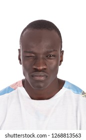 Young handsome Sudanese man winking with right eye no smile straight face, mouth closed face to camera in white tshirt, in portrait with copy space isolated on white background