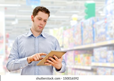 Young handsome supervisor with tablet pc in the mall