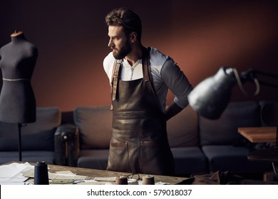 Young handsome tailor with beard in white shirt and leather apron standing near wooden table with threads in amazing atelier with antique furniture and mannequin on background