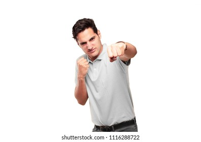 Young handsome tanned man with an angry, aggressive and menacing pose, ready for the fight, showing fists furiously and belligerently.