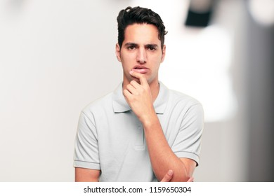 Young handsome tanned man with a goofy, dumb, silly look, feeling shocked and confused at a recent realization, not really understanding an idea.