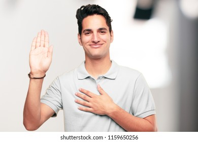 Young handsome tanned man smiling confidently while making a sincere promise or oath, solemnly swearing with one hand over heart.