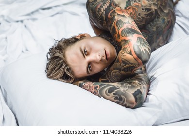 young handsome tattooed man having breakfast in bed in the open air outdoors in the garden, donuts and coffee for breakfast.
