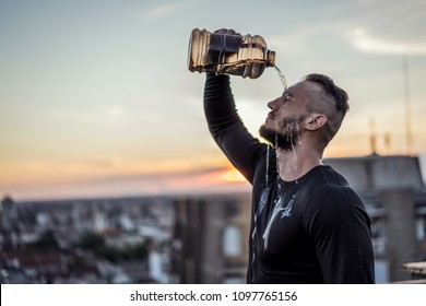 Young handsome tattooed man refreshing with water after training hard. Male sports outside on the top of the building. Outdoors recreation, stretching and training fit body.