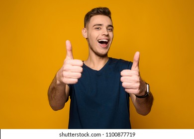 Young handsome thin guy shows thumbs up isolated on yellow background. Studio portrait.