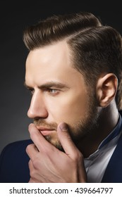 Young handsome thoughtful bearded caucasian man with blue eyes and a hand near chin. Perfect skin and hairstyle. Wearing blue suit.Studio portrait on gradient black background.