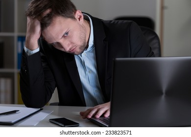 Young handsome tired man working at night in his office