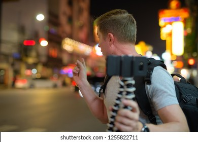 Young handsome tourist man vlogging in the streets of Chinatown at night