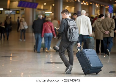 Young handsome traveler in 20s walking in modern airport terminal, using smartphone app in public wifi area, messaging, travelling with luggage bag, wearing casual style clothes, copy space
