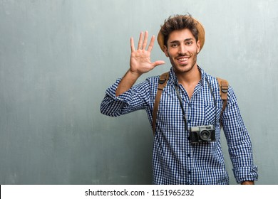 Young handsome traveler man wearing a straw hat, a backpack and a photo camera showing number five, symbol of counting, concept of mathematics, confident and cheerful
