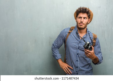 Young handsome traveler man wearing a straw hat, a backpack and a photo camera crazy and desperate, screaming out of control, funny lunatic expressing freedom and wild