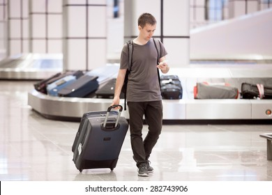 Young handsome traveller man in 20s leaving arrivals lounge of airport terminal building after collecting his baggage at conveyor belt, using smartphone app in public wifi area, messaging