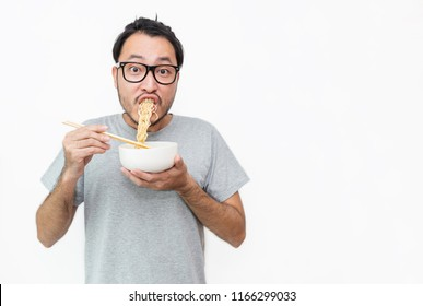 Young handsome trendy asian nerd man eating yummy hot and spicy instant noodle using chopsticks isolated on white background. Asian guy servile end of the month with cheap unhealthy food.