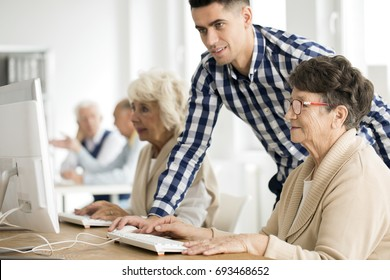 Young handsome tutor helping older lady having problem with computer task