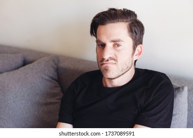 Young handsome unsatisfied man in black t-shirt sitting on a couch and looking at the camera