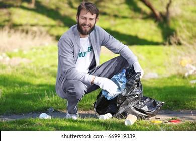 Young handsome volunteer picking up litter in park