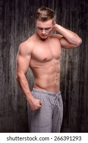Young handsome well formed sporty man demonstrating muscles with his arm raised up. Fitness concept