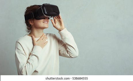 Young handsome woman wearing virtual headset. Excited Hipster using VR glasses. Grey concrete wall background