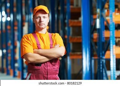 young handsome worker man in uniform in front of warehouse rack arrangement stillages
