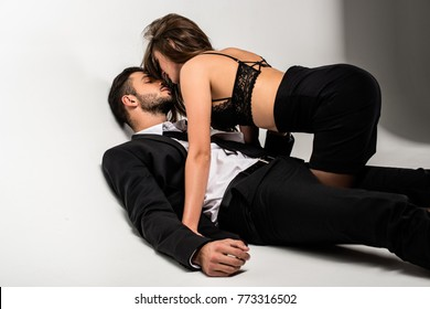 young handsone businessman with beautiful girl in skirt and lingerie lying on floor