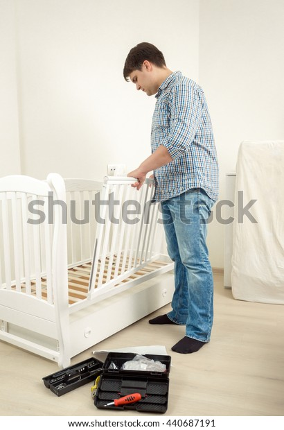 Young handyman assembling white baby crib in new apartment