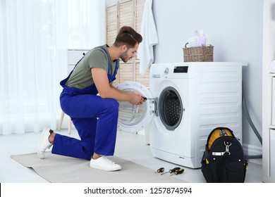 Young handyman fixing washing machine at home. Laundry day