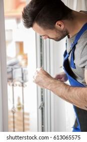 Young handyman repair window