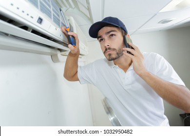 young handyman repairing air conditioning system calling for help