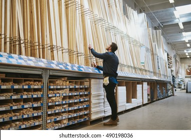 Young handyman selecting a length of cut timber from a rack in a hardware supply warehouse standing reaching up for his selection