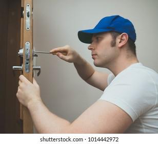 Young handyman in uniform changing door lock.