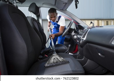 Young Handyman Vacuuming Car Front Seat With Vacuum Cleaner