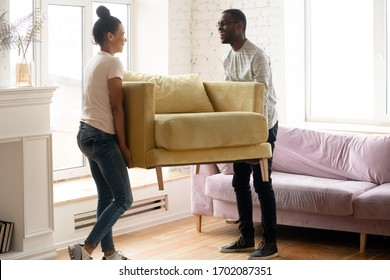Young happy african american couple moving and carry table. Attractive family of diverse woman and man relocation furniture in new home. Husband and wife perform permutation.