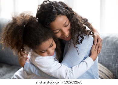 Young happy African American mom hug with small daughter making peace after fight, loving millennial mother or nanny embrace with little mixed race girl, reconcile after quarrel or conflict at home