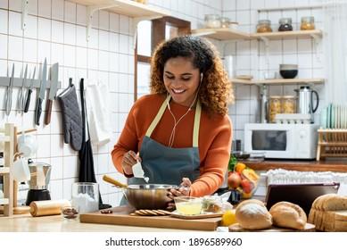 Junge, glückliche Afroamerikanerin, die beim Kochen mit Ohrhörer in der Küche, Hobby-Konzept kocht
