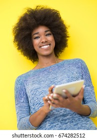 Young Happy African American Woman Using Digital Tablet  Isolated on a yellow background