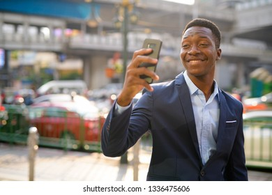Young happy African businessman taking selfie in the city