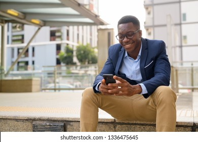 Young happy African businessman using phone while sitting outside the subway train station
