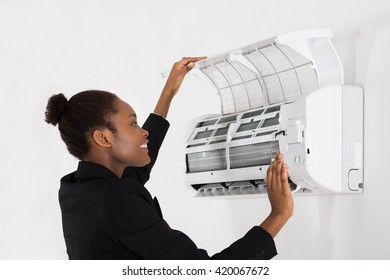 Young Happy African Businesswoman Checking Air Conditioner In Office