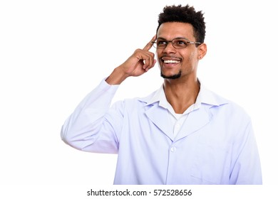 Young happy African man doctor smiling while thinking with finger on head