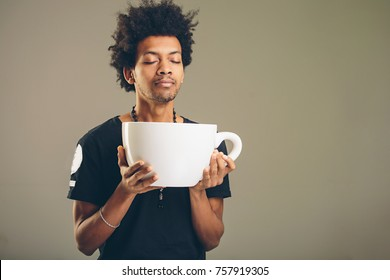 young happy african man holding a funny huge and oversized cup of black coffee in caffeine addiction concept