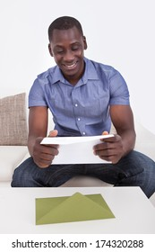 Young Happy African Man Reading Envelope At Home