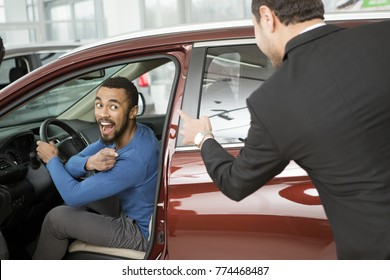 Young happy African man sitting in a new car at the dealership laughing at the salesman pointing fingers at him quarrel bullying emotional fun funny crazy stealing gesturing laughter positivity