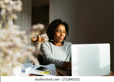 Young happy african woman with curly hair working from home on computer while sitting at table at home