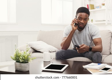 Young happy african-american man watching tv and talking on smartphone pointing with remote controller on tv-set, sitting on the couch, copy space