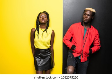 Young and happy afro american couple isolated on color background. Man and woman afro american have fun isolated on yellow and black