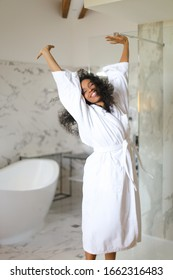 Young happy afro american woman wearing white bathrobe and dancing in hotel bathroom with marble walls. Concept of morning relax.
