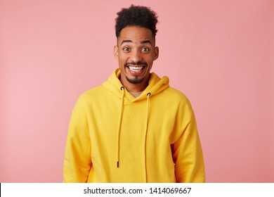 Young happy amazed african american guy in yellow hoodie, heard the news that his favorite band is coming to his city with a concert, broadly smiling and looking at the camera over pink background.