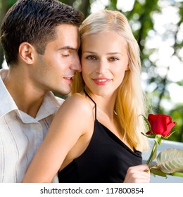 Young happy amorous cheerful couple with rose, outdoor